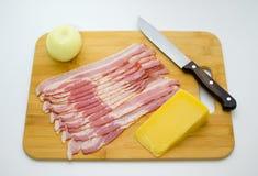 Rebanadas del tocino, queso parmesano, cebolla en la tajadera Cuchillo de talla imagen de archivo libre de regalías