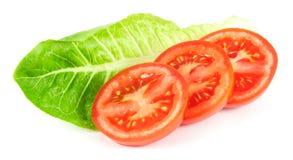 Rebanadas del tomate con la hoja de la ensalada Imagenes de archivo