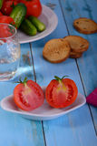 Rebanadas del tomate con las galletas en la tabla azul Foto de archivo libre de regalías