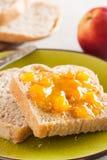 Rebanadas deletreadas del pan en un plato con el primer de la mermelada del melocotón Imagen de archivo