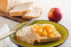 Rebanadas deletreadas del pan en un plato con la mermelada del melocotón Fotos de archivo