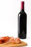 Rebanadas finas de jamón español del serrano y de botella de vino aislados en el fondo blanco Imagen de archivo libre de regalías