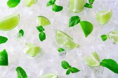Rebanadas frescas de cales y de menta verdes sobre los cubos de hielo machacados Fotos de archivo
