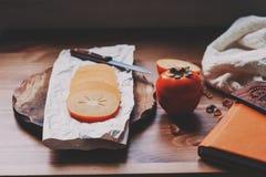 Rebanadas frescas del caqui en la tabla de madera con el cuaderno y el suéter hecho punto Fotos de archivo