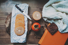 Rebanadas frescas del caqui en la tabla de madera con el cuaderno y el suéter hecho punto, visión superior Fotografía de archivo