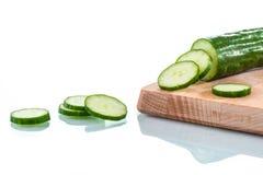 Rebanadas frescas del pepino en la tabla de cortar de madera Foto de archivo libre de regalías