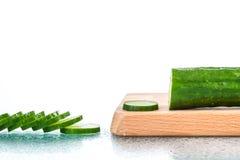 Rebanadas frescas del pepino en la tabla de cortar de madera Imagen de archivo libre de regalías