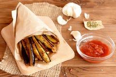 Rebanadas fritas curruscantes de la berenjena con un ajo, las especias y la salsa de tomate Foto de archivo