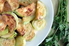 Rebanadas fritas del calabacín en la placa blanca con verdes Foto de archivo libre de regalías