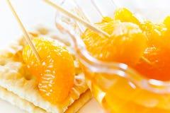 Rebanadas peladas de la mandarina en una galleta Foto de archivo