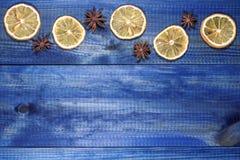 Rebanadas secadas del limón con anís de estrella en la tabla de madera azul foto de archivo libre de regalías