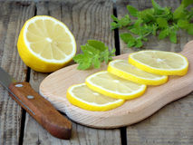 Rebanadas tajadas del limón en el tablero de madera, el cuchillo y la puntilla de la menta Fotografía de archivo libre de regalías