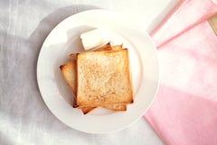 Rebanadas tostadas del pan con la palmadita de mantequilla para el desayuno Imagenes de archivo
