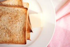 Rebanadas tostadas del pan con la palmadita de mantequilla para el desayuno Imagen de archivo libre de regalías