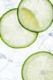Rebanadas verdes de la cal en los cubos de hielo Imagen de archivo