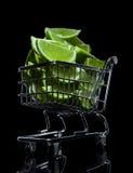 Rebanadas verdes de la cal en una carretilla miniatura del supermercado Fotos de archivo libres de regalías