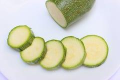 Rebanadas verdes de la calabaza en fila fotos de archivo