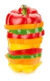 Rebanadas verdes, rojas y anaranjadas de la paprika aisladas en el backg blanco Fotografía de archivo libre de regalías