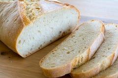 Rebanadas y barra de pan en la tabla de madera Foto de archivo libre de regalías