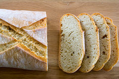 Rebanadas y barra de pan en la tabla de madera Foto de archivo