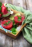 Rebanadas y bebida de la sandía en una tabla de madera rústica Foto de archivo libre de regalías