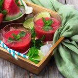 Rebanadas y bebida de la sandía en una tabla de madera rústica Foto de archivo