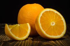 Rebanadas y entero anaranjados, en la tabla Foto de archivo