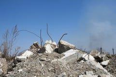 Rebar που κολλά επάνω από τους σωρούς των ερειπίων τούβλου Στο υπόβαθρο, μπορείτε να δείτε τα υπόλοιπα των λεσχών καπνού στοκ εικόνες