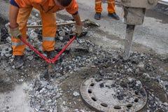Rebar de coupe de travailleur de la construction et bras de marteau piqueur images libres de droits