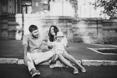Rebecca 6 Junge stilvolle Paare sitzen auf der Pflasterung in der alten Stadt Hübscher Junge glücklich mit seinen Eltern Lizenzfreie Stockbilder