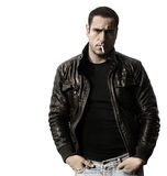 Rebel. Portrait of a rebel type guy in classic leather jacket with cigarette in mouth against white background Stock Photo