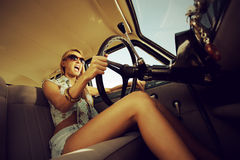 Rebel girl. Beautiful young woman driving vintage car Stock Photography