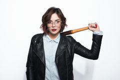 Rebel girl with batt on shoulder. Young stylish brunette in glasses and leather jacket posing with batt on shoulder on white background Stock Photos