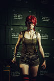 Rebel girl with grenade and molotov coctail. Redhead pretty military girl posing in a storage Stock Images