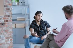 A rebel teenage boy with behavioral problems and criminal past t. Alking to a psychotherapist in a juvenile detention center royalty free stock images