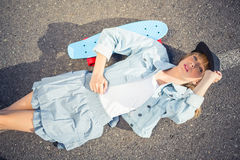 Rebellious blonde skater lying on the road Royalty Free Stock Photography