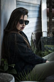 Rebellious girl with sunglasses. Rebel girl with sunglasses sitting by caravan in work zone Royalty Free Stock Photography