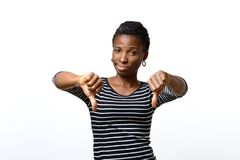 Rebellious negative woman giving a thumbs down. Rebellious negative african woman giving a thumbs down gesture with a frown to show her displeasure and register Royalty Free Stock Photos