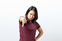 Rebellious negative woman giving a thumbs down Stock Images