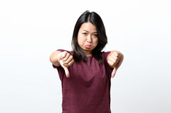 Rebellious negative woman giving a thumbs down Stock Photography