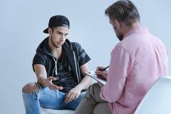 Rebellious spanish man talking to professional psychologist during meeting. Rebellious spanish men talking to professional psychologist during meeting stock photo