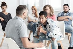 Rebellious spanish man listening to psychologist during group therapy for teenagers stock photos
