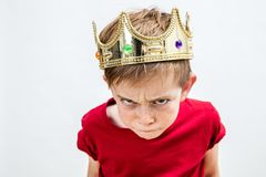 Rebellious spoiled kid with crown for mad attitude, high angle. Closeup of rebellious beautiful spoiled kid with frowning freckles wearing a king crown for mad royalty free stock image