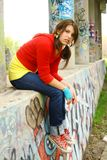 Rebellious teenage girl. A view of a teenage girl with a rebellious attitude, sitting under a concrete bridge that is covered with graffiti stock photography