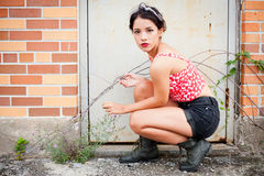 Rebellious teenage girl. Crouching by an old building stock photo