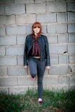 Rebellious teenager girl with red hair leaning on a wall Stock Photography