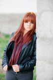 Rebellious teenager girl with red hair leaning on a wall Royalty Free Stock Photography