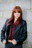 Rebellious teenager girl with red hair leaning on a wall Royalty Free Stock Image