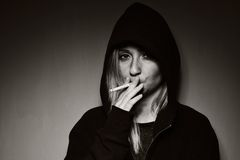 Rebellious teenager in a hooded sweatshirt. Rebellious teenager in a hooded sweatshirt smoking a cigarette Royalty Free Stock Photography