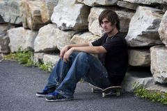 Rebellious young skateboarder sitting on board Stock Photography